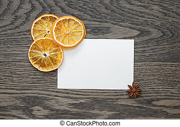 dried orange slices with paper card on oak table