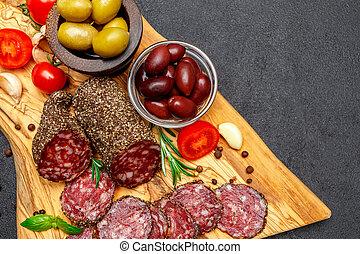 Dried organic salami sausage on wooden cutting board