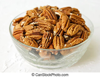 Dried pecan in a glass cup on a white textured background
