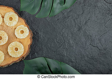 Dried pineapple rings on wooden piece. High quality photo