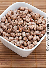 Dried pinto beans in a white bowl on a bamboo mat