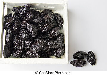 Dried plum fruits in a wooden box