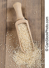 dried quinoa on wooden shovel
