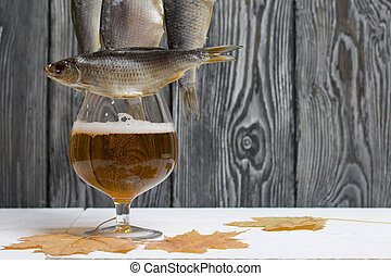Dried river fish hangs on a rope. Nearby is a glass of beer and dried maple leaves. There is a roach on the glass.