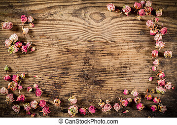 Dried rose flowers on wooden background