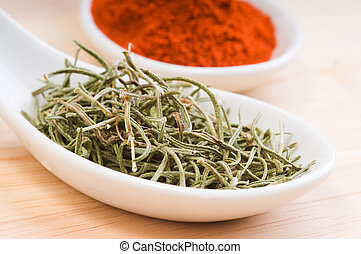 Dried Rosemary - Aromatic dried rosemary in a white spoon.
