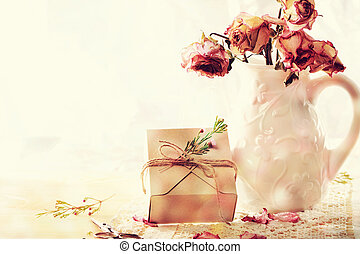 Dried roses in vase with gift box
