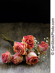 Dried roses on wood