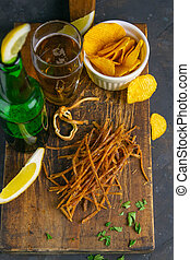Dried salmon cobweb with pepper with beer, lemon and potato chips on dark wooden board. Snack on fish with beer. Close-up