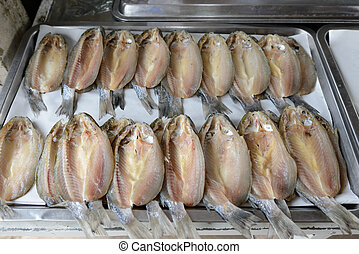 dried salted fish arranged on a tray