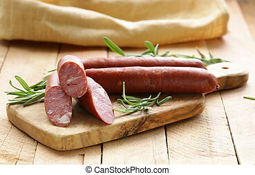 Dried sausage with  fresh rosemary on a wooden background