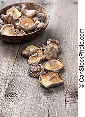 dried shiitake mushrooms in a bowl on the old wooden ...