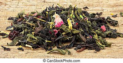 Dried tea leaves on wooden board.