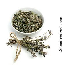 Dried thyme in a bowl and thyme twigs on white background