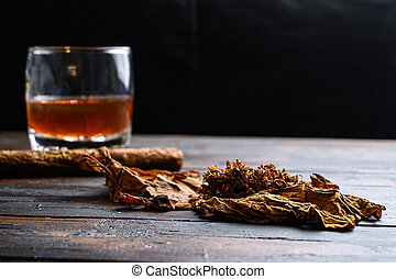 Dried tobacco leave and cut tobacco with cigar and whiskey rum on wood background on vintage dark table. side view space for text