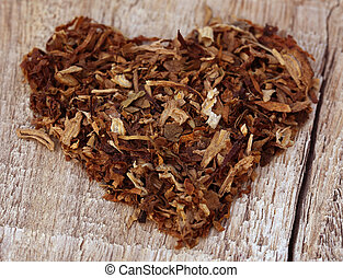 Dried tobacco leaves decorated in heart shape on wooden...