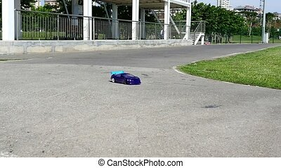 Drift RC model car spins on track in Summer. Exiting world...
