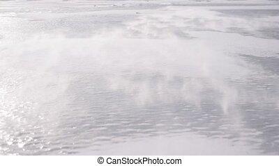 Drift snow blown by heavy wind on ice in winter