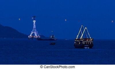 drifting ship along bay at night against ropeway and...