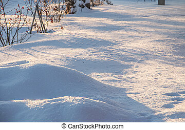 drifts of pure snow in the rays of the evening sun at sunset