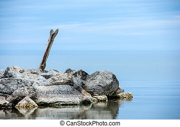 driftwood log in rocks and water - driftwood log in rocks on...