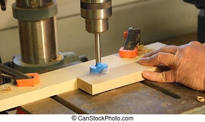 drill press drilling holes in a cabinet makers board