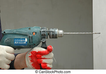 Drill - worker is drilling an opening in a wall