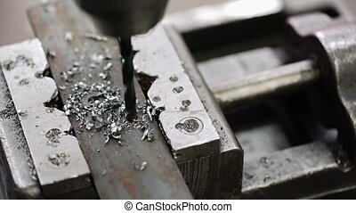 Drilling a hole into a piece of metal, close-up