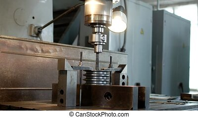 Drilling a hole with a drilling machine in a metal workpiece...