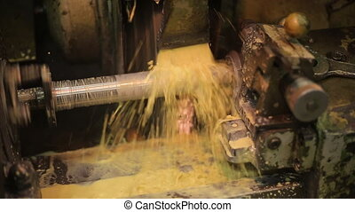 Drilling a metal blank on automatic old and dirty machine with coolant.