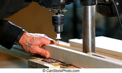 Drilling a plywood at wood factory close-up