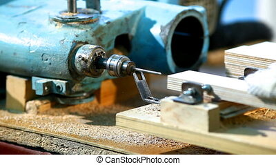 Drilling a plywood at wood factory close-up
