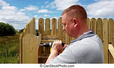 Drilling a screw into the wooden fence.