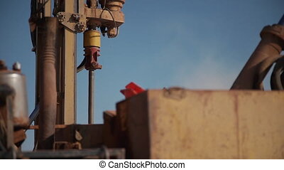 Drilling equipment in working process in gas factory on background of blue sky.
