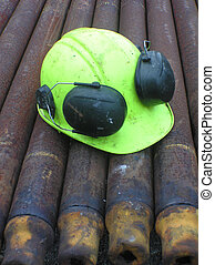 yellow hard hat on layer of pipes for a drill string at an oil well