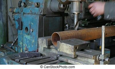 Drilling machine makes holes in the pipe - The drilling...