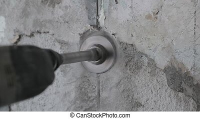 drilling of concrete with a round construction crown. worker drills a wall with a perforator. Slow motion video