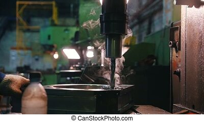Drilling work on metal parts. There is metal shavings and...
