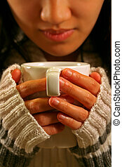 Drink coffee - A woman holding a cup of coffee