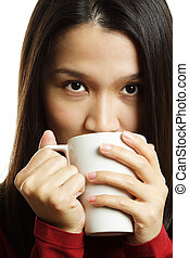 Drink coffee - A beautiful young woman holding a coffee cup
