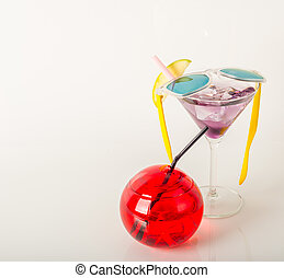 drink decorated with fruit, martini glass, drink straw and ice cubes
