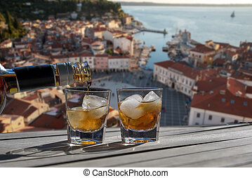 Drink for two on a terrace overlooking a small town on the ...