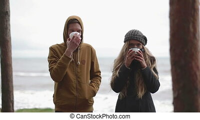 Drink in cold weather. man and woman drink tea from a thermos
