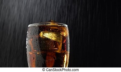 Drink into a glass with ice and drip drops of water . Black...