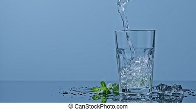 Drink mojito with lime, mint and ice pour into a glass on a blue glossy background. Slow motion 2k video shooted on 240 fps