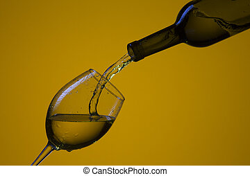 Drink Pouring Out of Bottle On The Right Hand Side to Wineglass with Colorful Liquid and Droplets.
