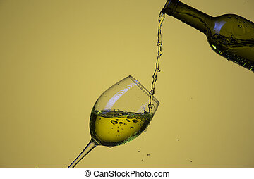 Drink Pouring Out of Bottle On The Right Hand Side to Wineglass with Colorful Liquid and Droplets. Isolated Over Lemon Color Background