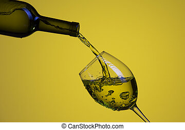 Drink Pouring Out of The Bottle On The Left Hand Side to Whineglass with Colorful Liquid and Droplets. Isolated Over Yello Background.