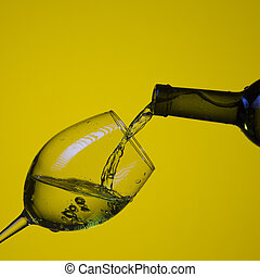 Drink Pouring Out of The Bottle On The Right Hand Side to Wineglass with Colorful Liquid and Droplets. Isolated Over Lemon Color Background