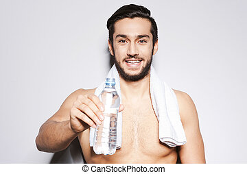 Drink some water! Young muscular man stretching out a bottle with water in his hand and smiling while standing against grey background